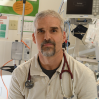 Dr. Chris Milburn sitting in an emergency department