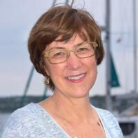 Lady with short brown hair and glasses, sailboat rigging in background
